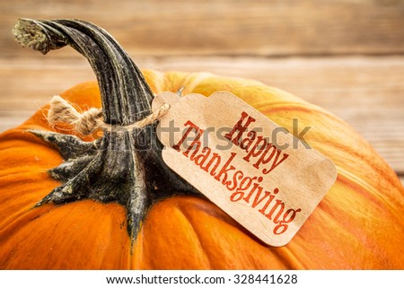 pumpkin with a Happy Thanksgiving paper price tag -  holiday shopping concept - stock photo