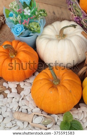 Pumpkin with pumpkin seeds on wood background