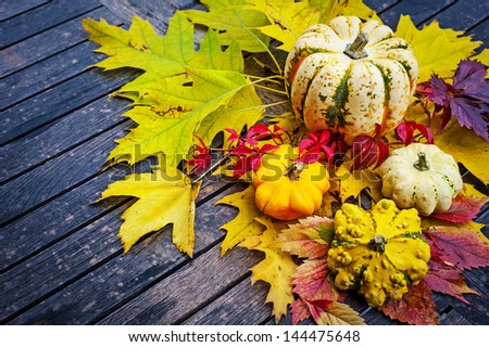 pumpkins and autumn foliage on a old wooden table - stock photo