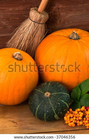 Pumpkins and gourd with berries and broomstick