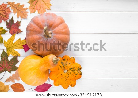 pumpkins and orange squash with fallen colorful leaves on white colored wooden table, top view, free space for text