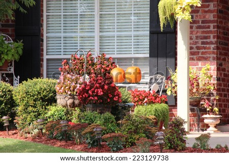 Pumpkins and other decorations near a house - stock photo