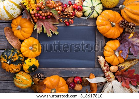 Pumpkins and variety of squash around a chalkboard - stock photo