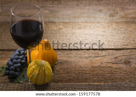 pumpkins, grapes and wine glass on old wooden - stock photo