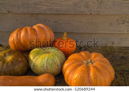 Pumpkins in basket on rustic vintage background on wooden table