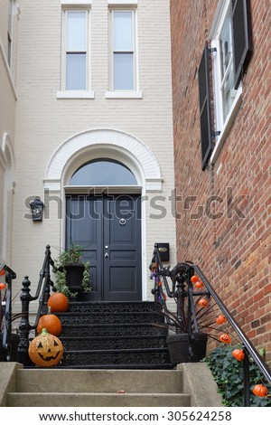 Pumpkins in front door to celebrate Thanksgiving and Halloween  - stock photo
