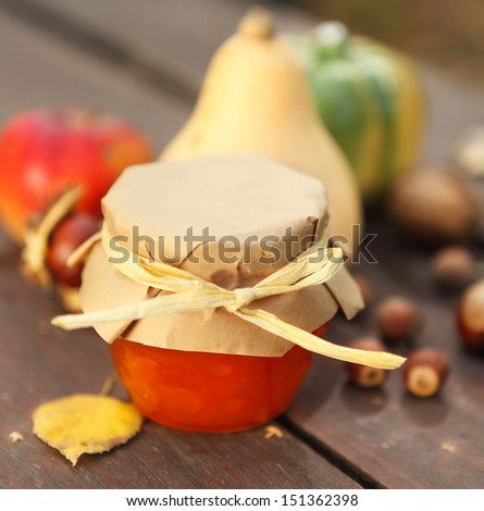 Pumpkins, jam, nuts and apples on garden table - stock photo