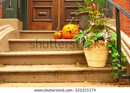 Pumpkins near the door during Halloween season - stock photo