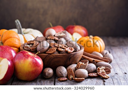 Pumpkins, nuts, indian corn and apples on a rustic table - stock photo