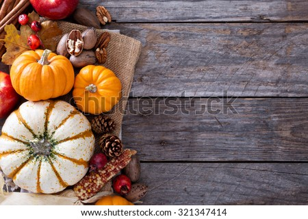 Pumpkins, nuts, indian corn and apples on a rustic table overhead corner frame with empty space - stock photo