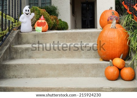 Pumpkins on front steps of home during Halloween / Thanksgiving season  - stock photo
