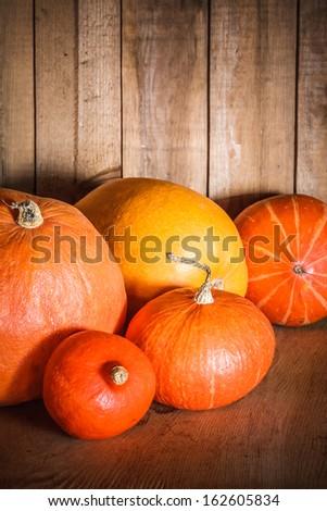 Pumpkins on grunge wooden backdrop, background table. Autumn, halloween, pumpkin, copyspace - stock photo