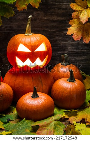 Pumpkins pile with autumn leaves - stock photo