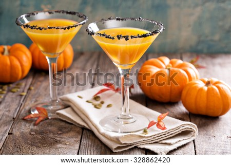 Pumpkintini pumpkin martini coctail with black salt rim for fall and halloween parties - stock photo