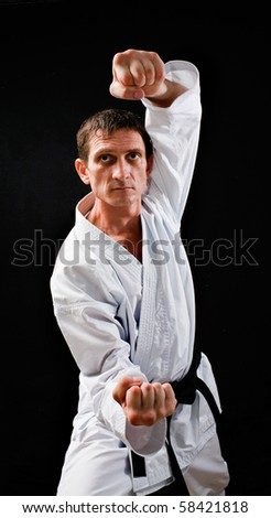 punch.figure in the karate fighting stance on a black background.hand-to- hand fighting - stock photo