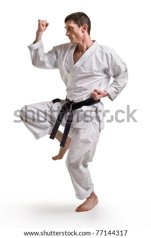 punch.figure in the karate fighting stance on a black background.hand-to-hand fighting - stock photo
