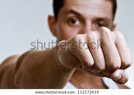 Punch with clenched fist of a handsome young man, showing off his muscles and fit physique in an aggressive fight pose, shot against grey background. - stock photo