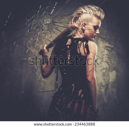 Punk girl behind broken glass with a baseball bat - stock photo