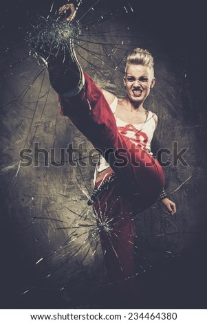 Punk girl breaking glass with her boot - stock photo