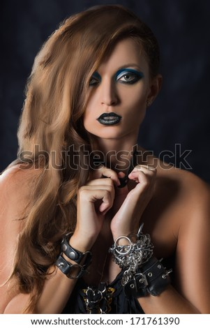 punk girl in heavy boots in bracelets and chains - stock photo