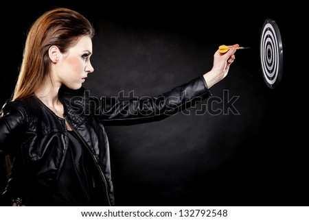 punk girl with arrow dart and target black backgruond - stock photo