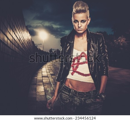 Punk girl with cigarette outdoors at night - stock photo