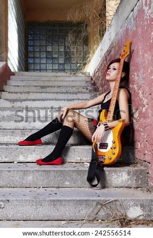 Punk/rock woman guitar player posing on street - stock photo