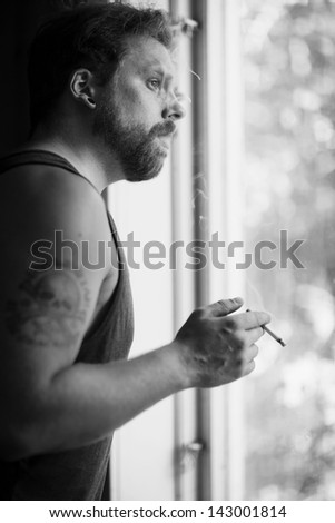 Punk rocker standing by the window and smoking cigarettes and thinking. - stock photo