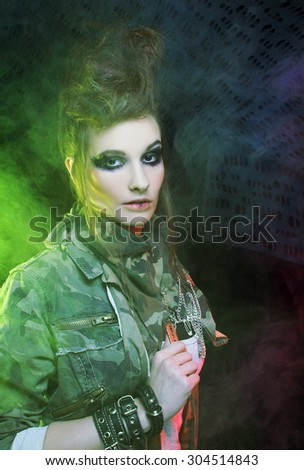 Punk. Young woman with smokey eyes and with artistic hairstyle posing with smoke
