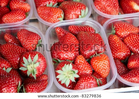 Punnets of strawberries for sale in an outdoor market