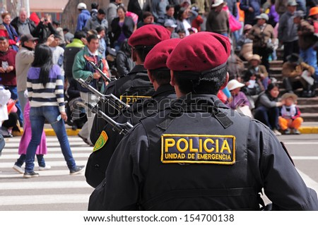 PUNO, PERU - MAY 19: Policemen stand on the main city square as they arrive at the parade on May 19, 2013 in Puno, Peru. - stock photo