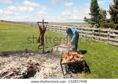 PUNTA ARENAS, CHILE-Nov. 13, 2016:  At an estancia not far from Punta Arenas, a gaucho demonstrates the barbecuing and carving of a lamb.