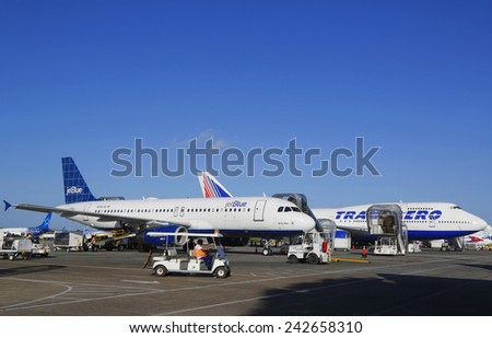 PUNTA CANA, DOMINICAN REPUBLIC - DECEMBER 30, 2014: Jetblue Airlines Airbus 320 and Transaero Boeing 747 at Punta Cana International Airport.  - stock photo