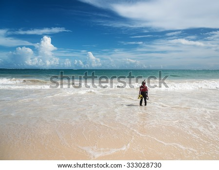 Punta Cana, Dominican Republic - October 9th 2015: Unknown man in costume for diving holds metal detector and prepare to dive. A lot of people search for lost bijouterie on beaches as a hobby or main - stock photo