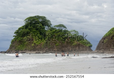 PUNTA LEONA, COSTA RICA - SEPTEMBER 6, 2008: People standing in sea at the beach in Punta Leona, Costa Rica. Punta Leona is a leading surfer hotspot with pristine beaches. - stock photo
