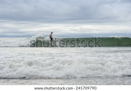 PUNTA LEONA, COSTA RICA - SEPTEMBER 6, 2008: Young man surfing on ocean wave at the beach in Punta Leona, Costa Rica. Punta Leona is a leading surfer hotspot with pristine beaches. - stock photo