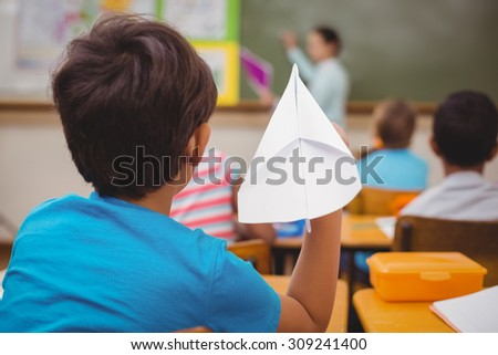 Pupil about to throw paper airplane at the elementary school - stock photo