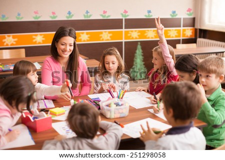 Pupil boys and girls sitting together around the table in classroom and drawing. With them is their young and beautiful teacher. She teaches children and is smiling - stock photo