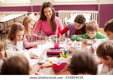 Pupil boys and girls sitting together around the table in classroom and drawing. With them is their young and beautiful teacher. She teaches children and smiling - stock photo