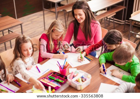 Pupil boys and girls sitting together around the table in classroom and drawing. With them is their young and beautiful teacher. She teaches children and is smiling. - stock photo