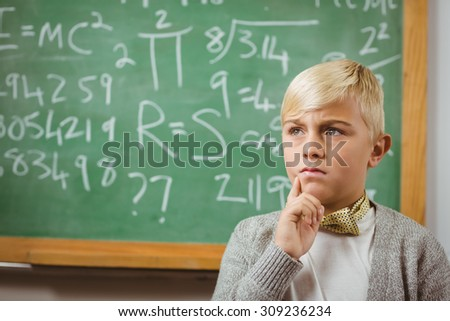 Pupil dressed up as teacher thinking in front of chalkboard in a classroom