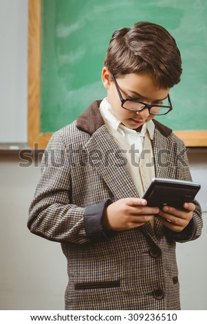 Pupil dressed up as teacher using calculator in a classroom - stock photo
