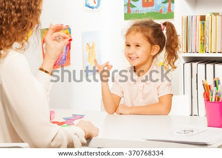 Pupil exercises putting fingers as her teacher - stock photo
