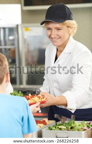 Pupil In School Cafeteria Being Served Lunch By Dinner Lady - stock photo