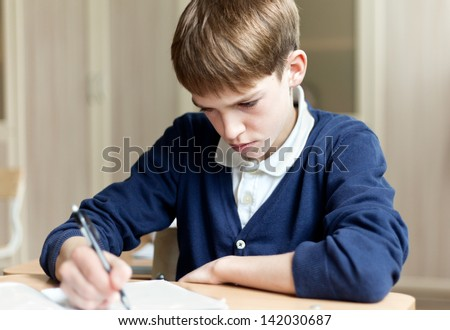 Pupil in uniform sitting at  desk in school classroom