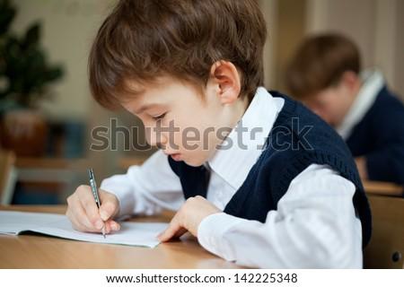 Pupil in uniform sitting at  desk in school classroom - stock photo
