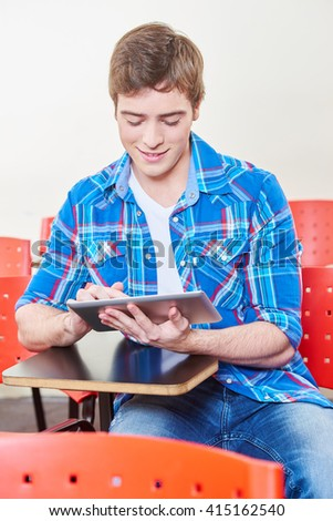 Pupil learns with a tablet in class and smiles - stock photo