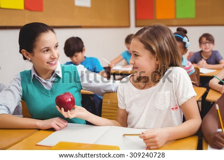 Pupil offering an apple to teacher at the elementary school - stock photo
