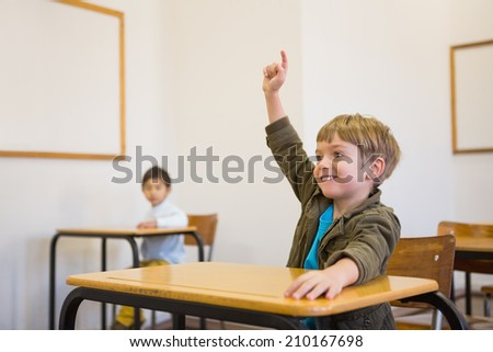 Pupil raising his hand at his desk at the elementary school - stock photo