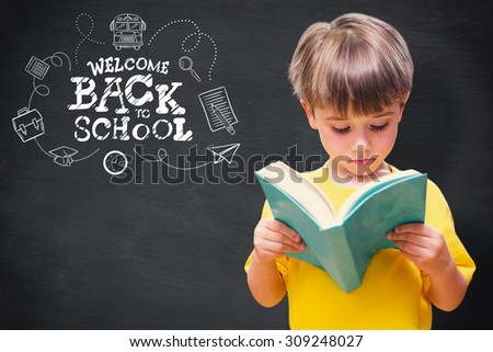 Pupil reading book against blackboard